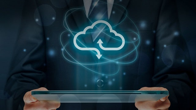 PADS professional cloud software. Image with human holding pad with cloud image populating the air. Digital display.
