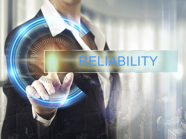 """Hand touching glowing dial, text overlay """"Reliability"""" 